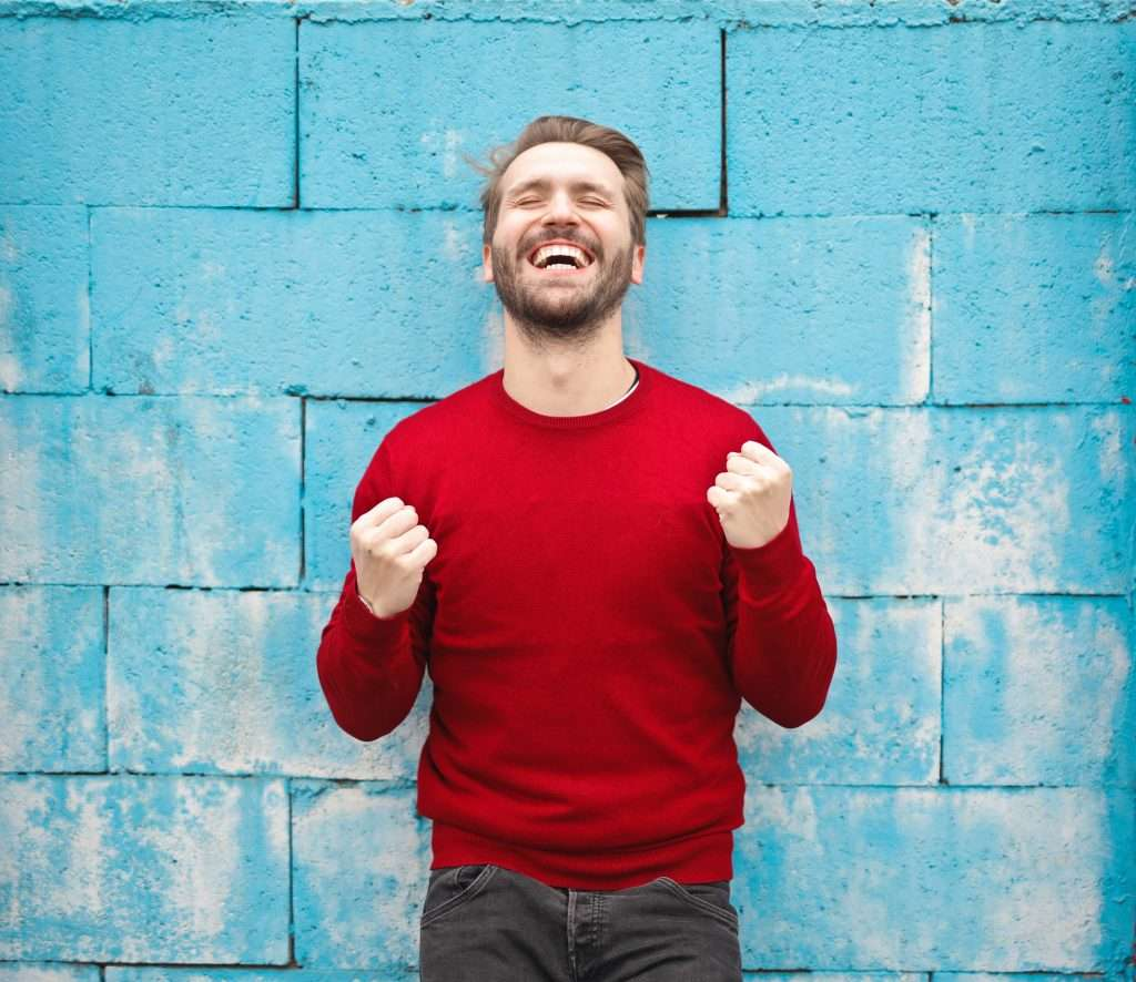 A happy man smiling against a blue brick wall.